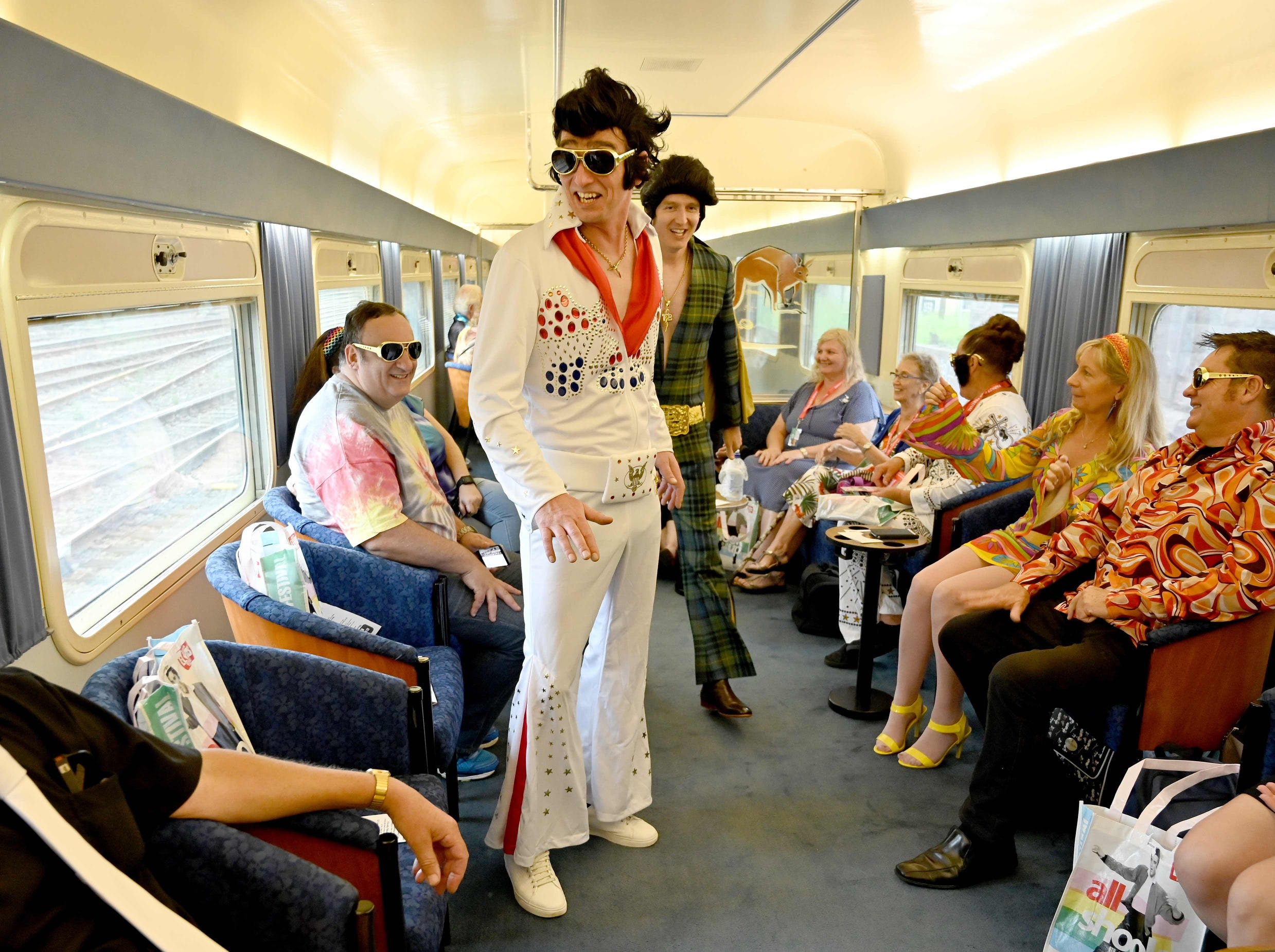 Elvis fans  enjoy the scene on a train a heading to The Parkes Elvis Festival.