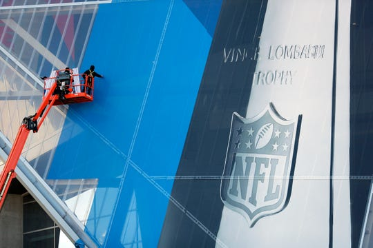 Workers hang banners on Mercedes-Benz Stadium in preparation for the NFL Super Bowl football game  Jan. 10 in Atlanta.