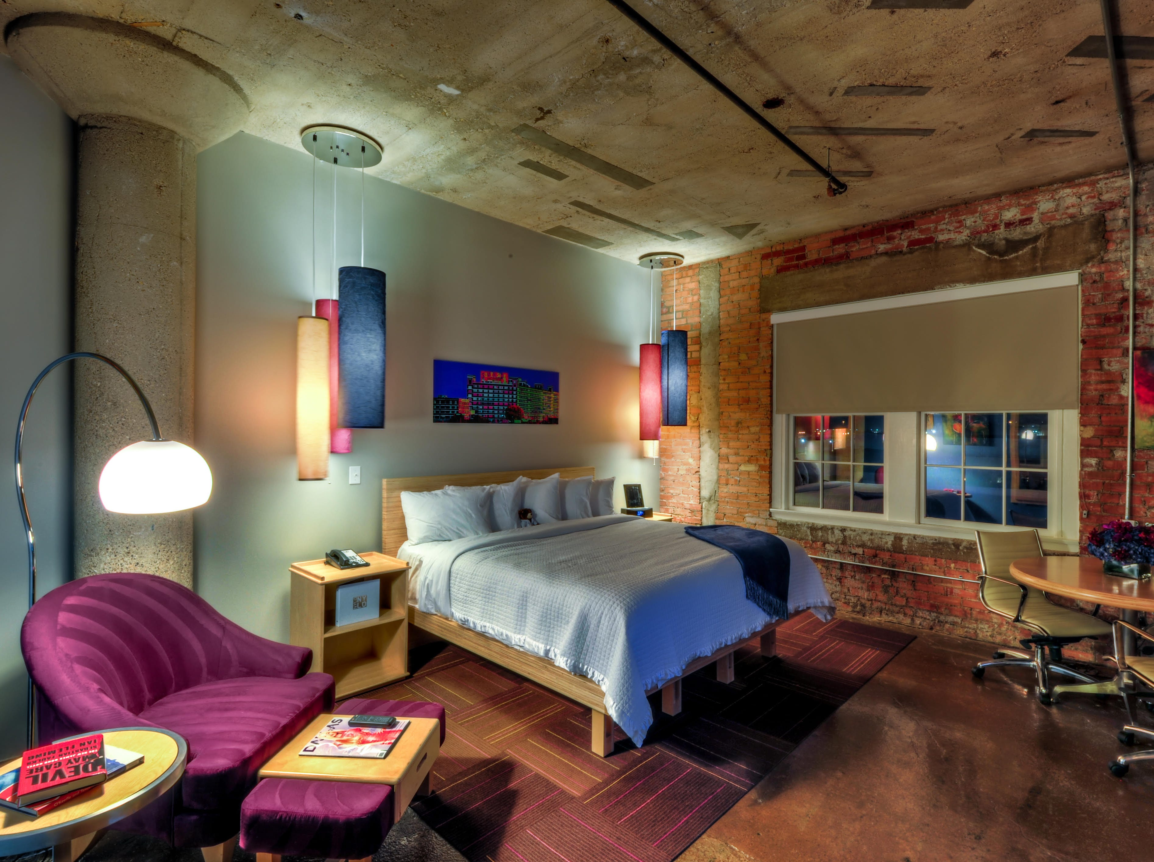 Guestrooms and suites at the CANVAS Hotel Dallas are loft-like with 10- to 15-foot high ceilings, concrete flooring, exposed brick, and industrial elements and fixtures.