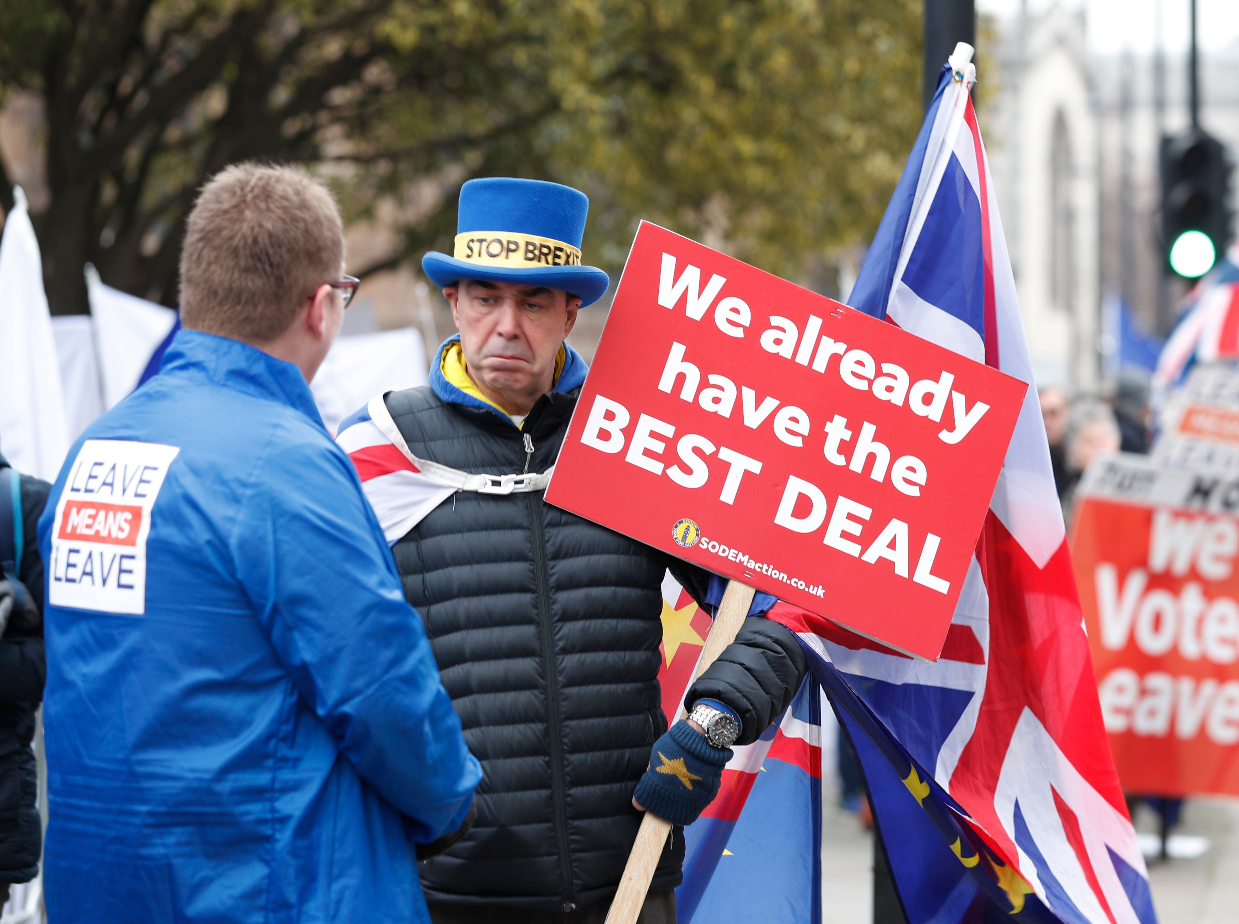 Pro-Brexit, left, and anti-Brexit, right, protesters debate their views outside parliament in London, Thursday Jan. 10, 2019. Prime Minister Theresa May's proposed Brexit deal seems widely disliked by both pro-European and pro-Brexit politicians, threatening the exit agreement and future relations with EU.