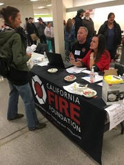 Volunteers give out $250 cash cards to victims of the Camp fire in California, which destroyed the town of Paradise in November of 2018. The California Fire Foundation set up a table in Chico, California at an intake center for victims of the fire, to hand out the cards.