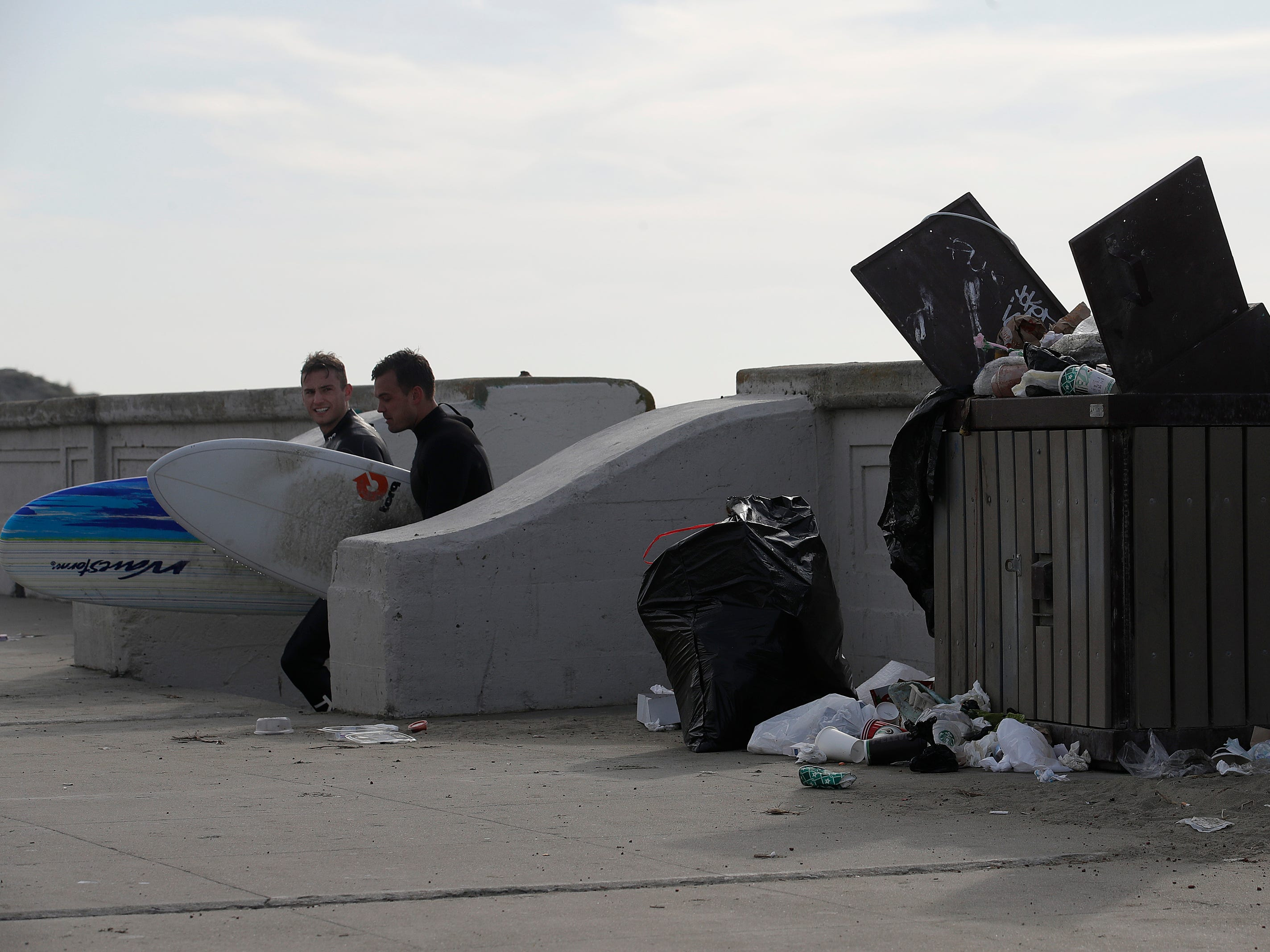 Two surfers walk past an open garbage bin and piles of trash at Ocean Beach in San Francisco, Jan. 3, 2019.