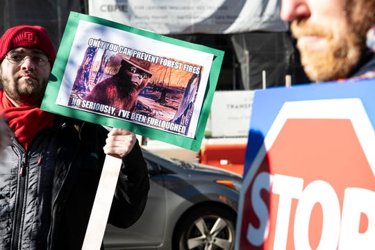 """At a rally Jan. 8 in Washington, protester Andrew Minton holds a sign featuring U.S. Forest Service icon Smokey Bear saying, """"Only you can prevent forest fires. No seriously, I've been furloughed."""""""