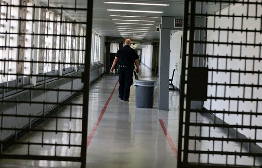Rikers Island juvenile detention facility officer walks down a hallway of the jail.