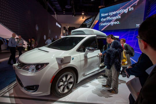 People look at the Waymo car, formerly the Google self-driving car project.