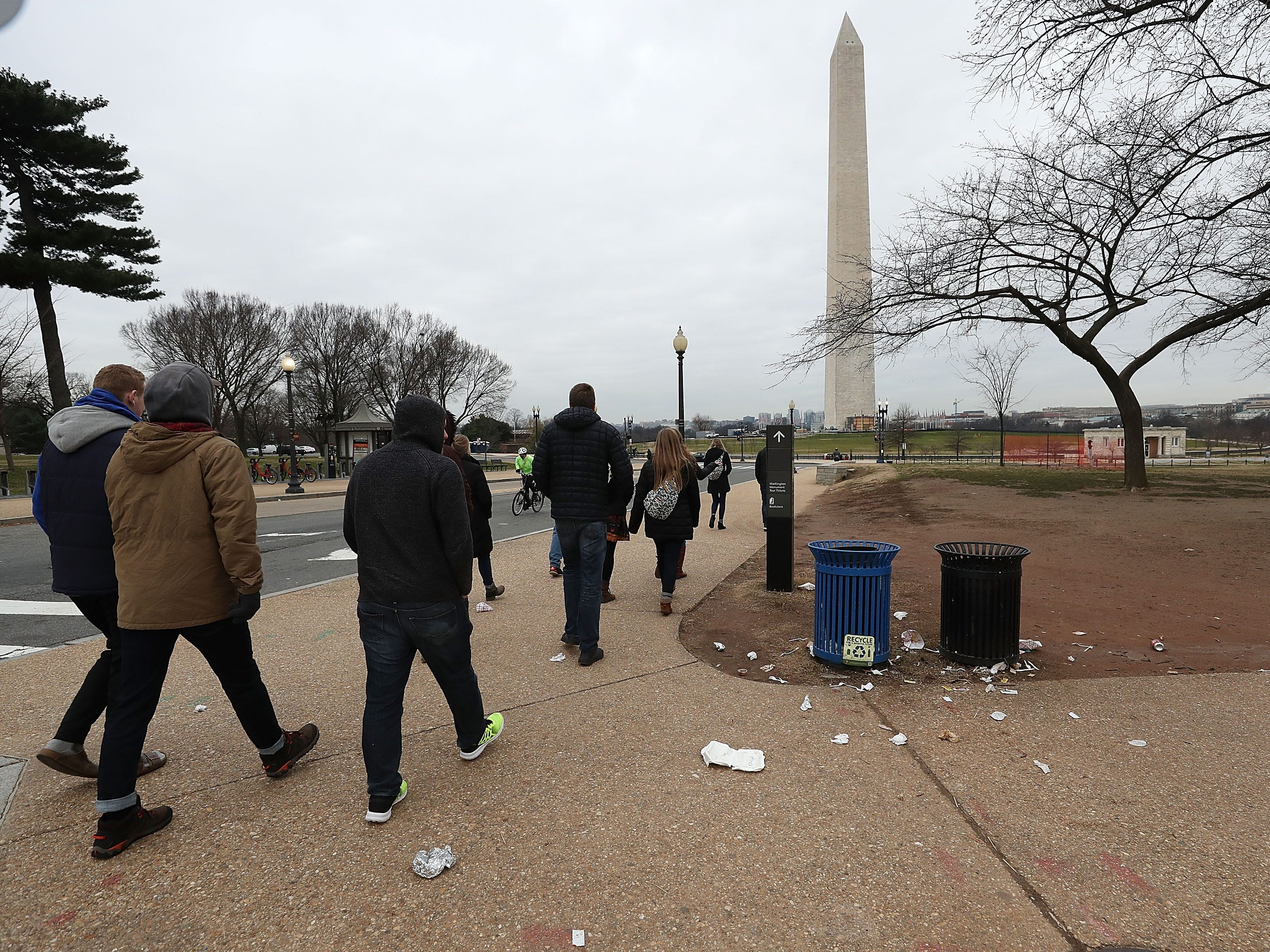 Tourist walk past trash laying on the ground of the National Mall on Jan. 2, 2019 in Washington, DC.