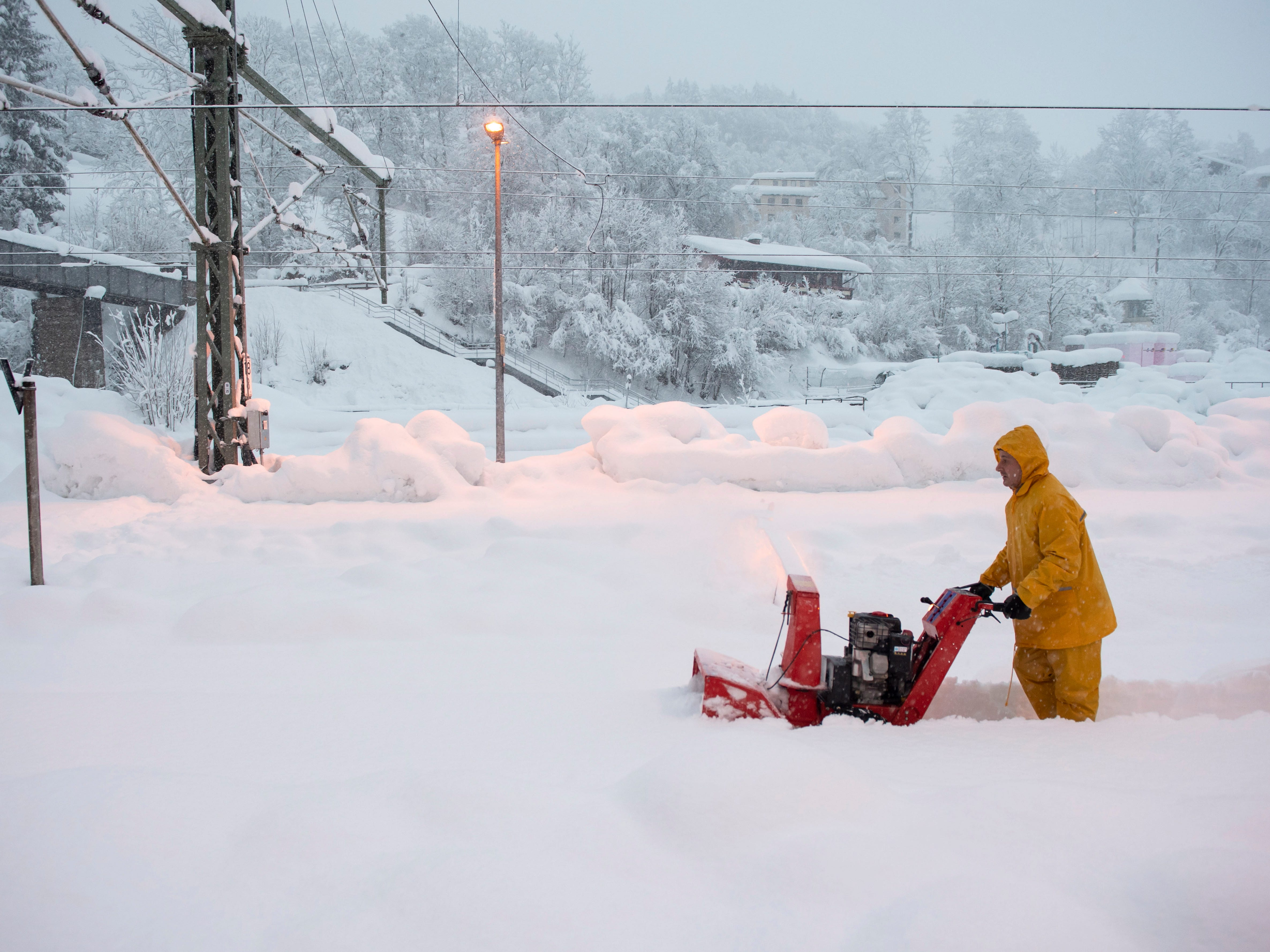 A man uses a snow blower to free a platform at the station in Berchtesgaden, Bavaria, Germany, Jan. 10, 2019.