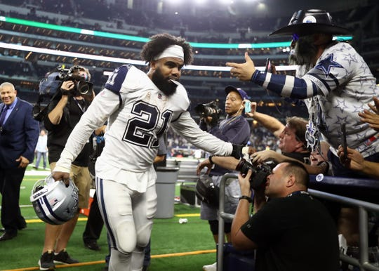 Dallas Cowboys running back Ezekiel Elliott (21) celebrates with fans after a victory against the New Orleans Saints at AT&T Stadium.