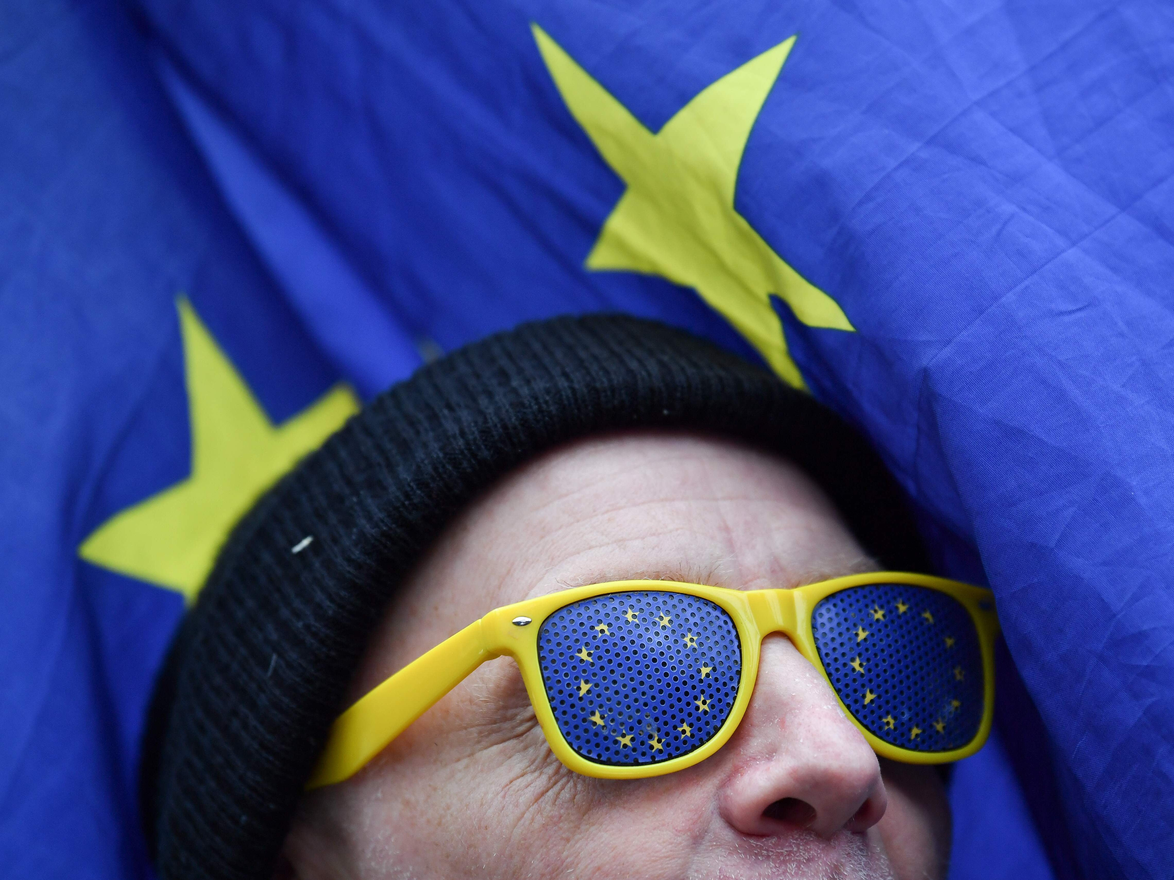 """An anti-Brexit protester is seen wearing glasses with EU flag motifs with an EU flag in the background outside the Houses of Parliament in London on Jan. 10, 2019. Britain's business minister on Thursday warned that the prospect of crashing out of the European Union without an agreement would be """"disastrous"""" for the country, as fractious MPs prepare to vote on a contentious Brexit deal."""