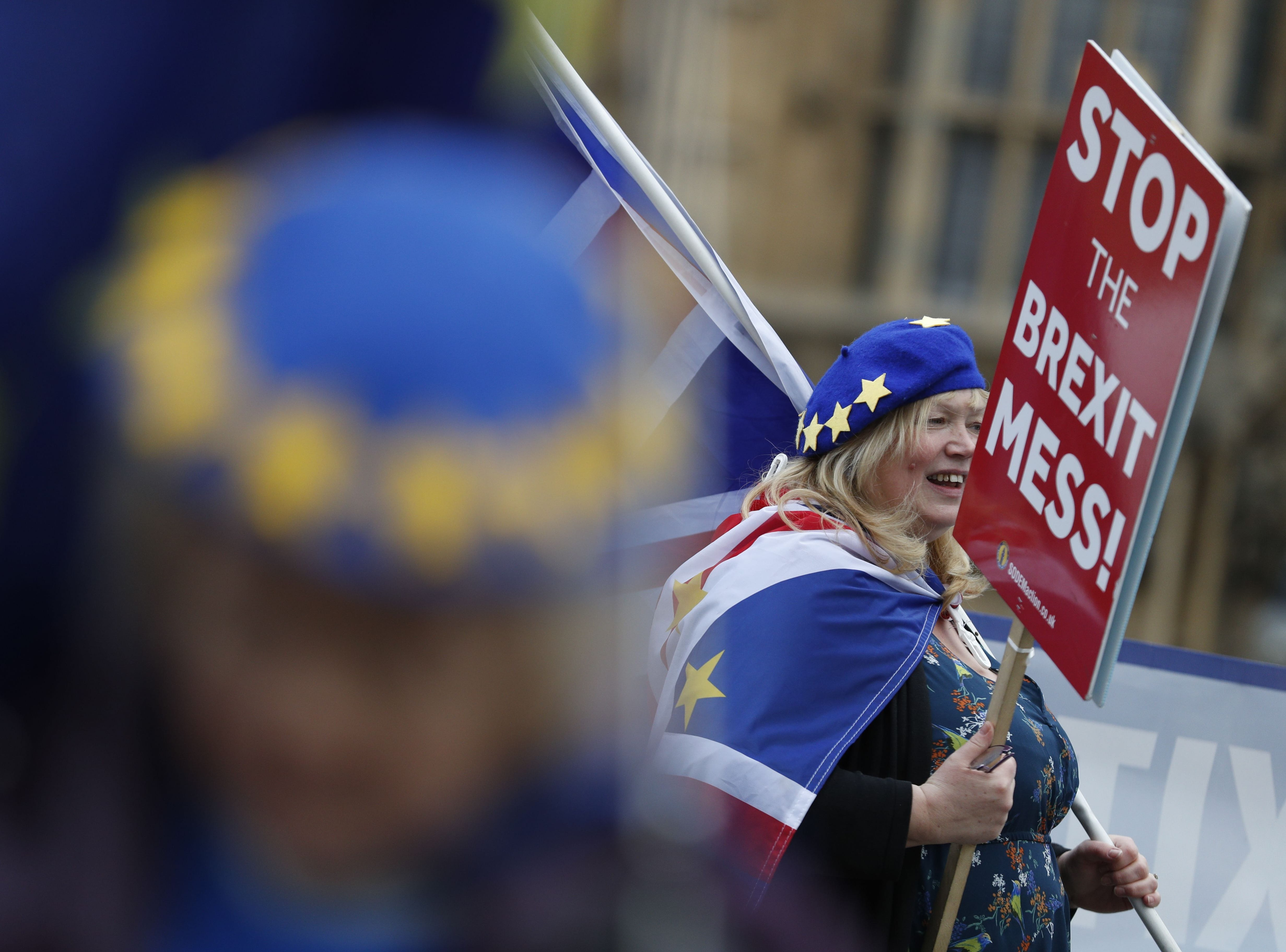 An anti-Brexit protester wearing attire decorated with EU flag motifs holding a placard stands outside the Houses of Parliament in London on Jan. 10, 2019.