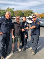 Firefighters give a victim of the Woolsey fire in Los Angeles county a $250 gift card to help with day-to-day expenses. The cards are a program of the California Fire Foundation, which in the last two months of 2018 gave out $2.6 million in pre-loaded cards to wildfire victims in the state.