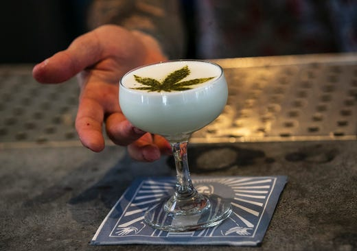 Maxwell Reis, beverage director serves a drink containing Cannabidol CBD extract with a marijuana leaf motif at the Gracias Madre restaurant in West Hollywood, Calif. The hemp-derived CBD extract is popping up in everything, from cosmetics to chocolate bars to bottled water to bath bombs to pet treats.