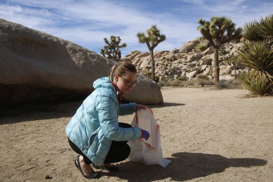 Katie Duron, a volunteer, collects garbage at Joshua Tree National Park, Calif. on Jan. 8, 2019.