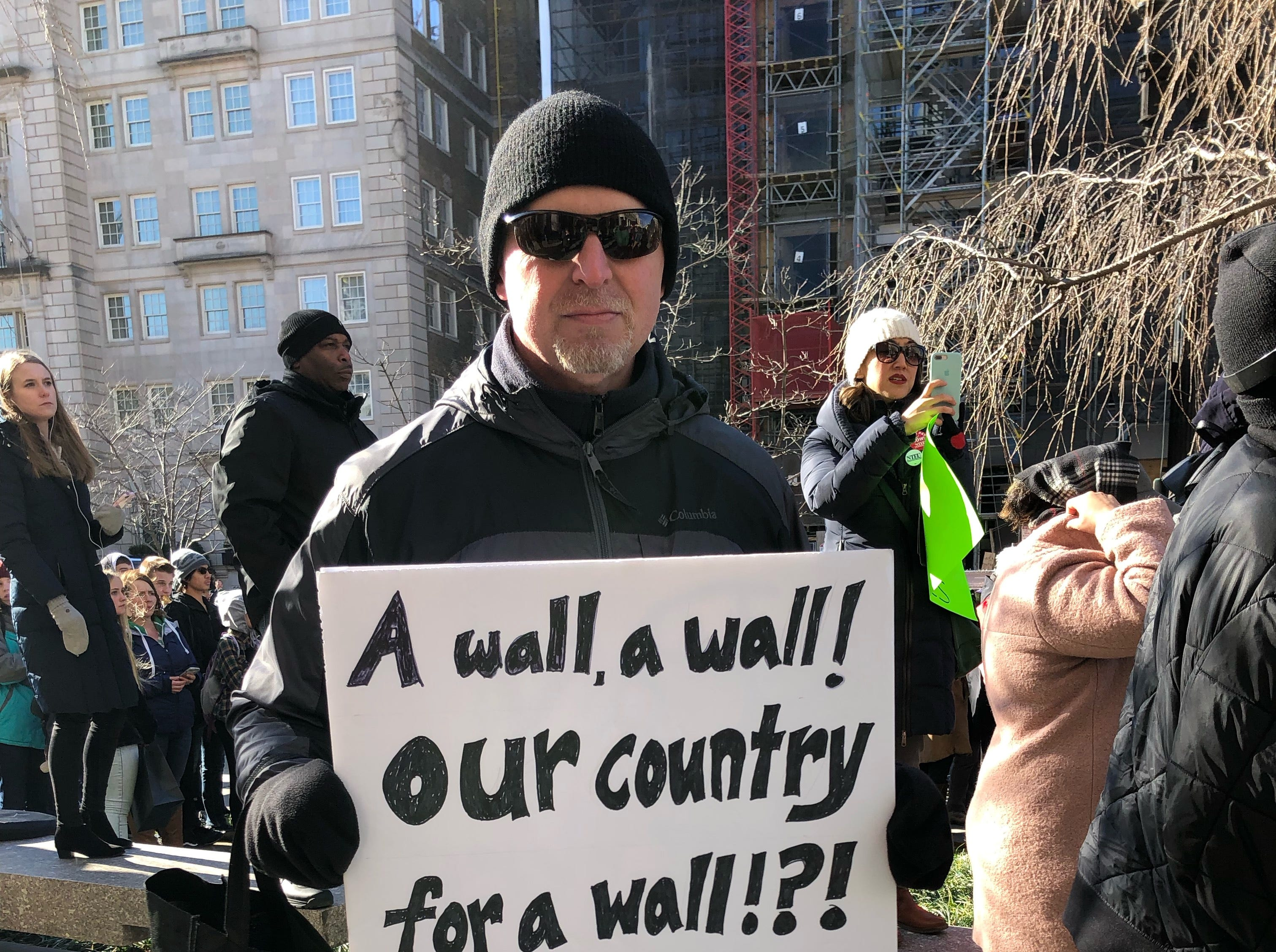 Anthony Jernigan, a Coast Guard environmental protection specialist, held a sign that said ÒA wall, a wall! Our country for a wall!?!Ó in Washington, D.C. on Thursday as federal workers rallied for their jobs.