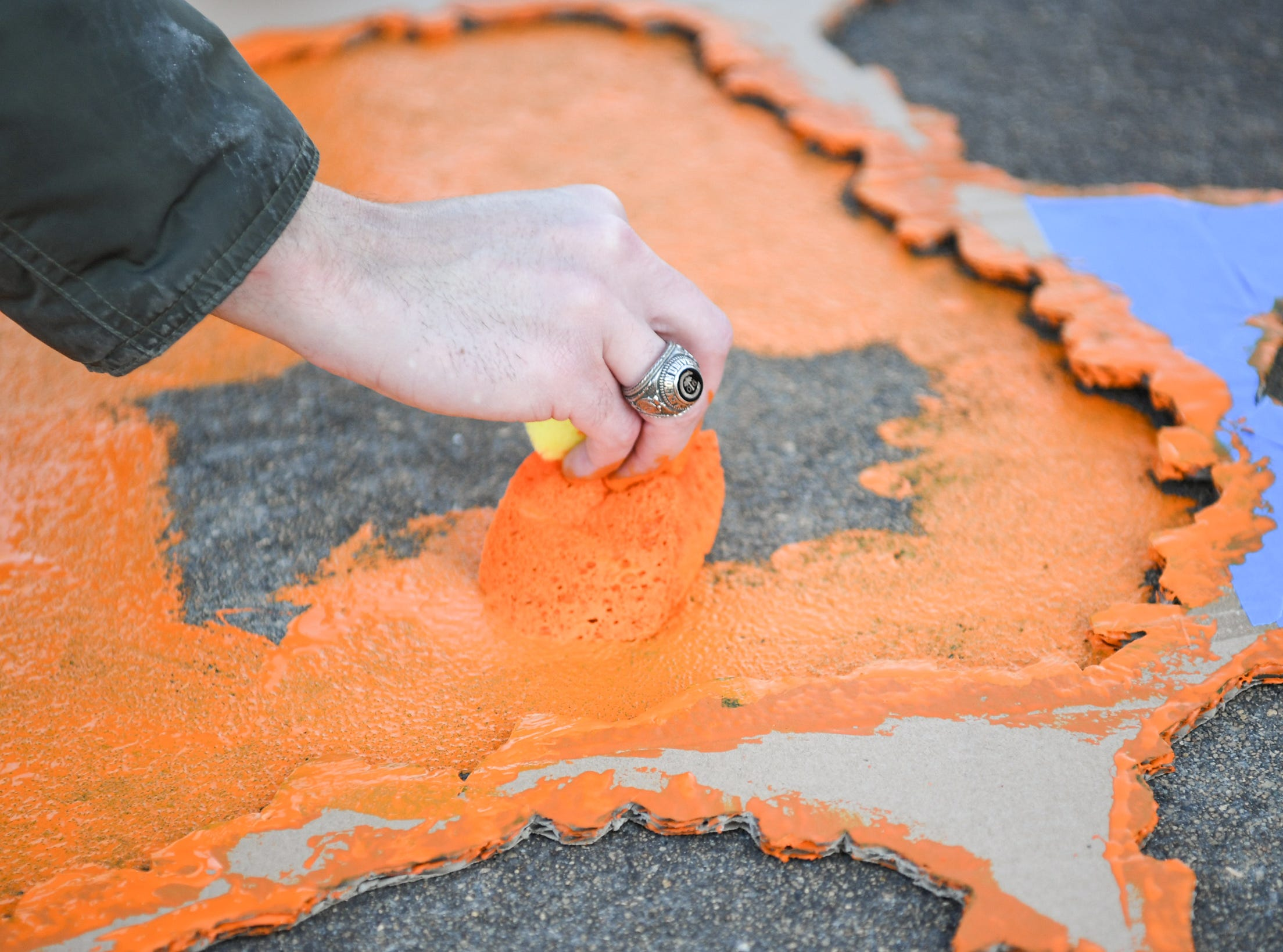 Blake Sanders, West Pelzer mayor, starts painting a tiger paw in the walkway of Eric Smith in West Pelzer Friday. Sanders, planning on painting 40 of them around town on walkways and driveways of those who have asked him through social media.