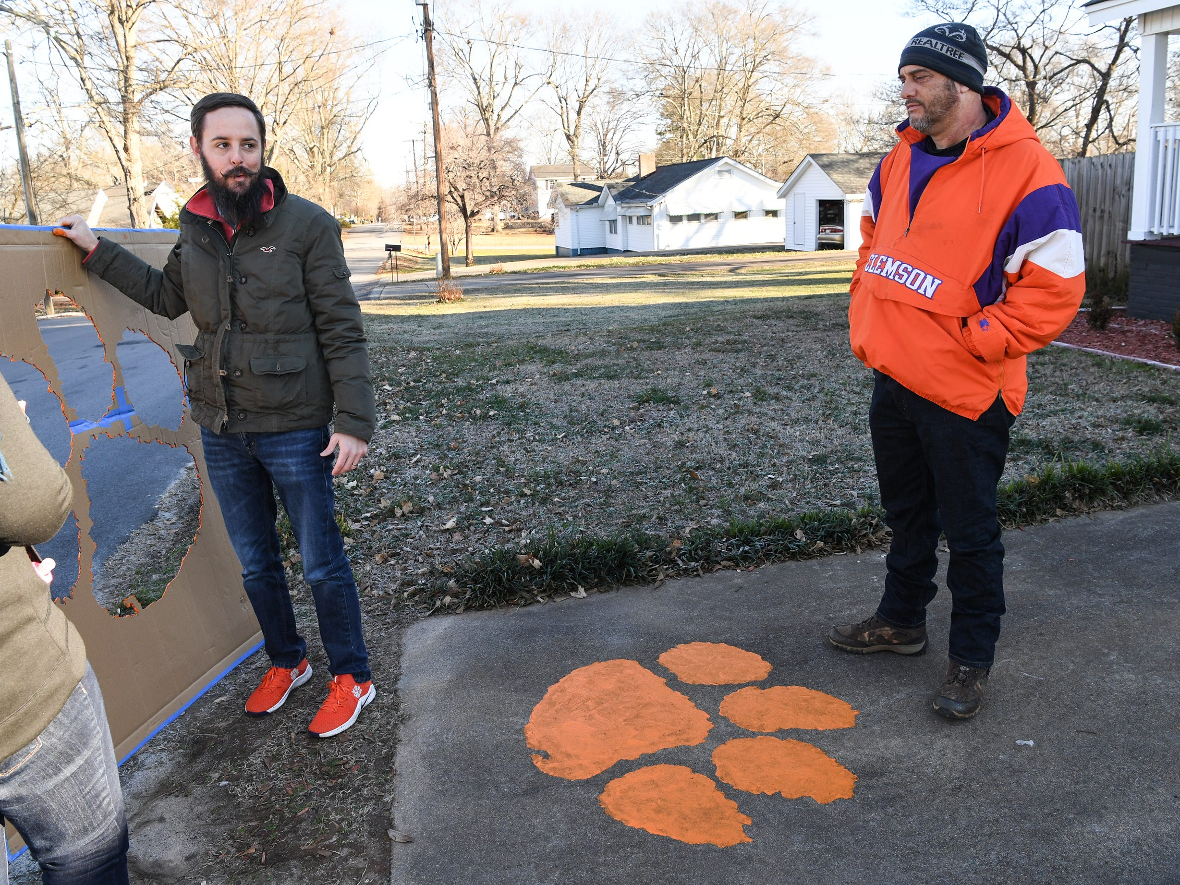 Blake Sanders, West Pelzer mayor, talks with Eric Smith, right, in West Pelzer after painting a tiger paw on his walkway Friday. Sanders, planning on painting 40 of them around town on walkways and driveways of those who have asked him through social media.