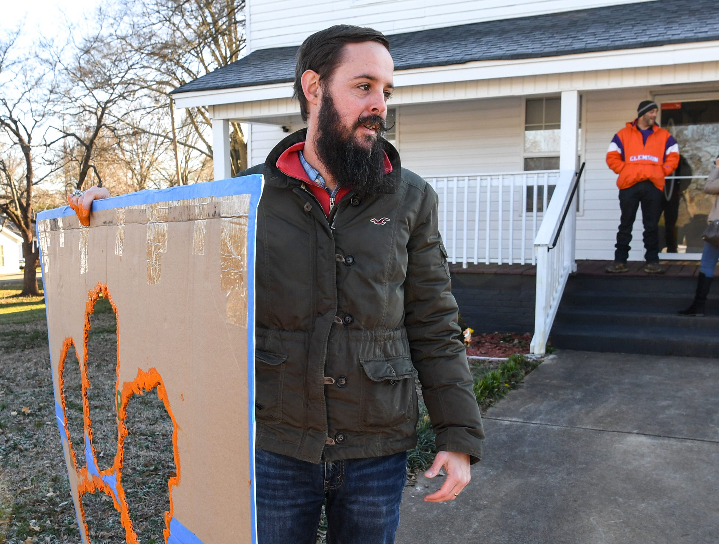 Blake Sanders, West Pelzer mayor, starts painting a tiger paw in the walkway of Eric Smith, right, in West Pelzer Friday. Sanders, planning on painting 40 of them around town on walkways and driveways of those who have asked him through social media.