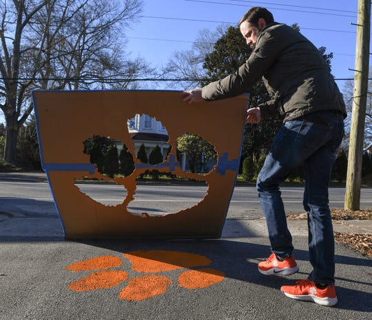 Blake Sanders, West Pelzer mayor, finishes painting a tiger paw in his driveway in West Pelzer Friday. Sanders, planning on painting 40 of them around town on walkways and driveways of those who have asked him through social media.