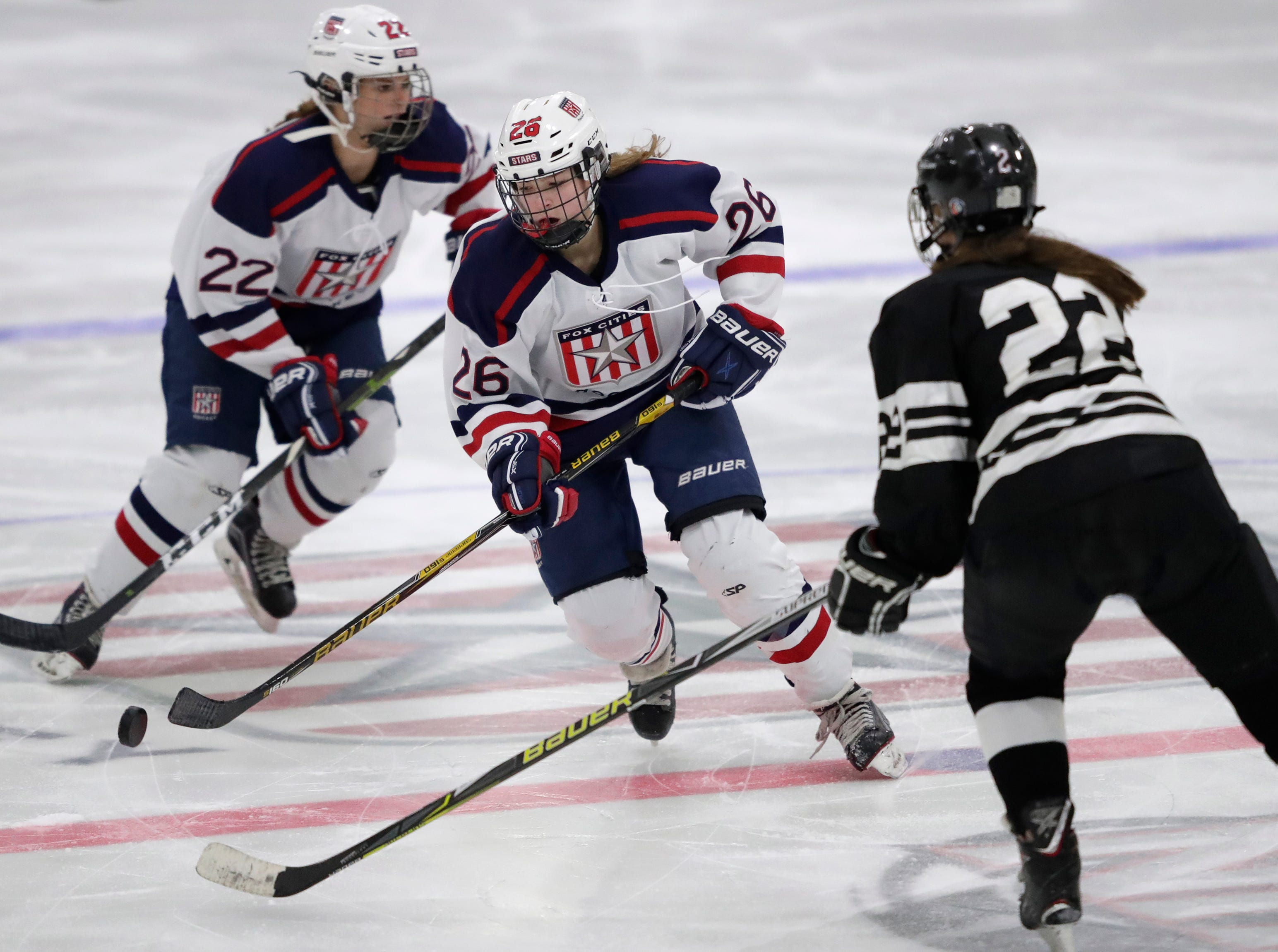Fox Cities Stars' McKayla Zilisch (26) looks to pass the puck against the Warbirds' Drew Deanovich (22) during their girls hockey game Thursday, January 10, 2019, at Tri-County Ice Arena in Fox Crossing, Wis. 