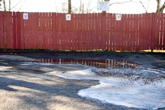 Puddles are half frozen in a parking area on Haywood Road next to Rainbow Community School where a man was shot and killed and the scene cleaned up on Jan. 11, 2019.