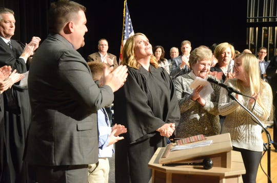 Judge Tomak looks upward after taking the oath of office during the ceremony Friday.