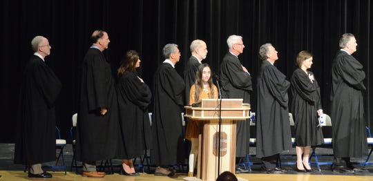 The assembled judges face the flag as Audrey Anthony, a Harper Creek seventh grade students sings the national anthem.