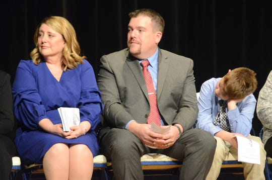 Judge Tomak, her husband, Jonathan Galbreath and son, Nicholas, listen to speeches on Friday.
