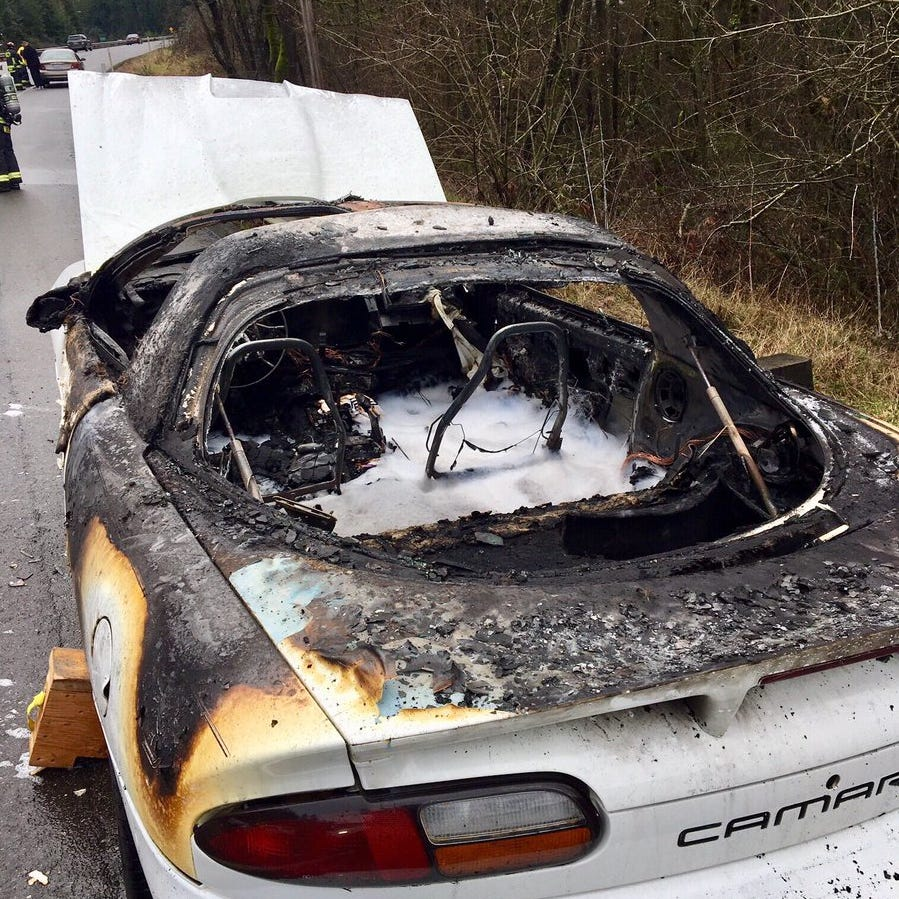 Passers-by pull man on fire from car