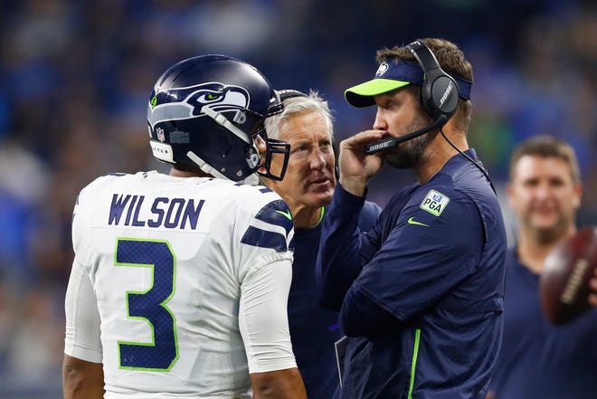 Seahawks quarterback Russell Wilson, here talking with offensive coordinator Brian Schottenheimer and head coach Pete Carroll last October, is reportedly seeking a complicated contract that would be tied to league revenues.