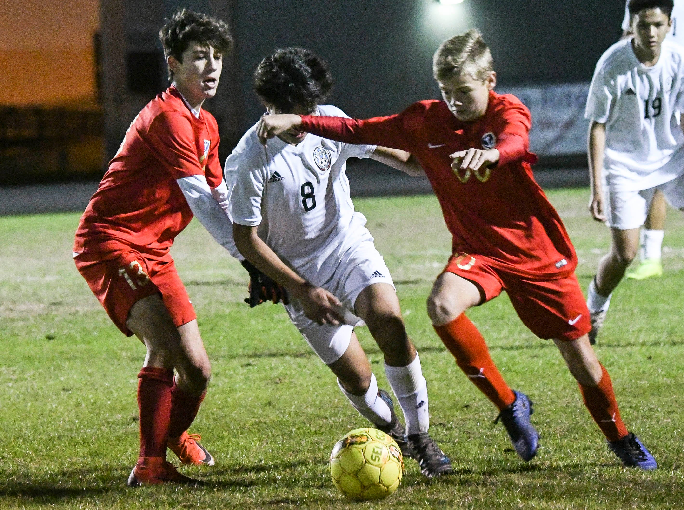 Jaxon Supernaw (left) and Logan Collins of Eau Gallie battle with Andrew Inocencio of Rockledge during Thursday's game in Melbourne.