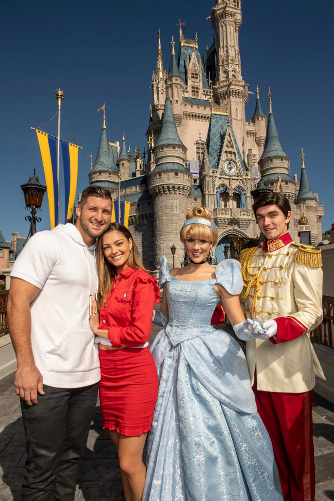 Professional athlete and sports analyst Tim Tebow and fiancé Demi-Leigh Nel-Peters strike a pose with Cinderella and Prince Charming at Magic Kingdom Park at Walt Disney World Resort in Lake Buena Vista, Fla., Friday, Jan. 11, 2019, while celebrating their recent engagement with family and friends.