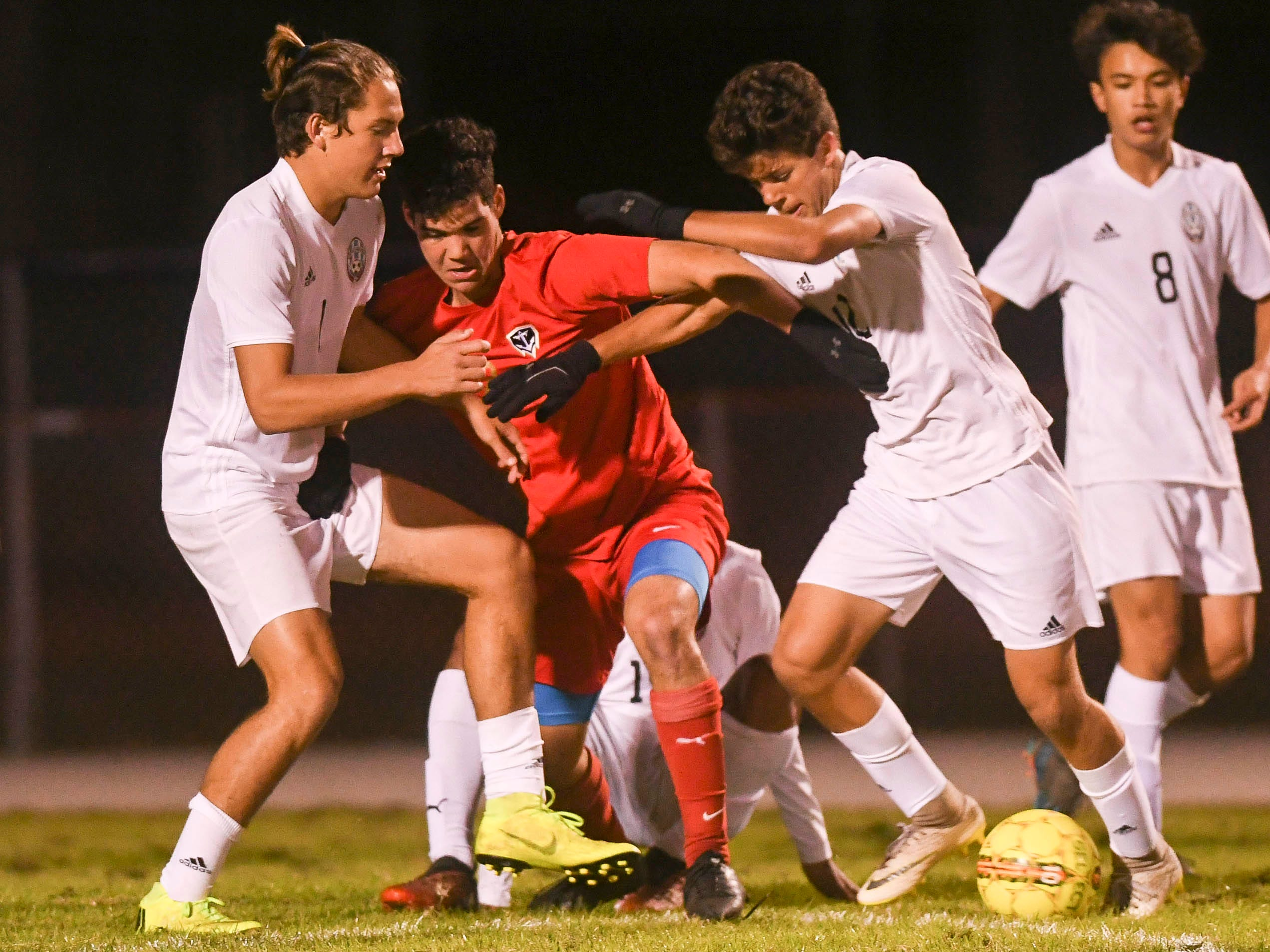 Richie Chamberlin (left) and Luis Esteban Son (right) tie up Markus Mills of Eau Gallie during Thursday's game in Melbourne.