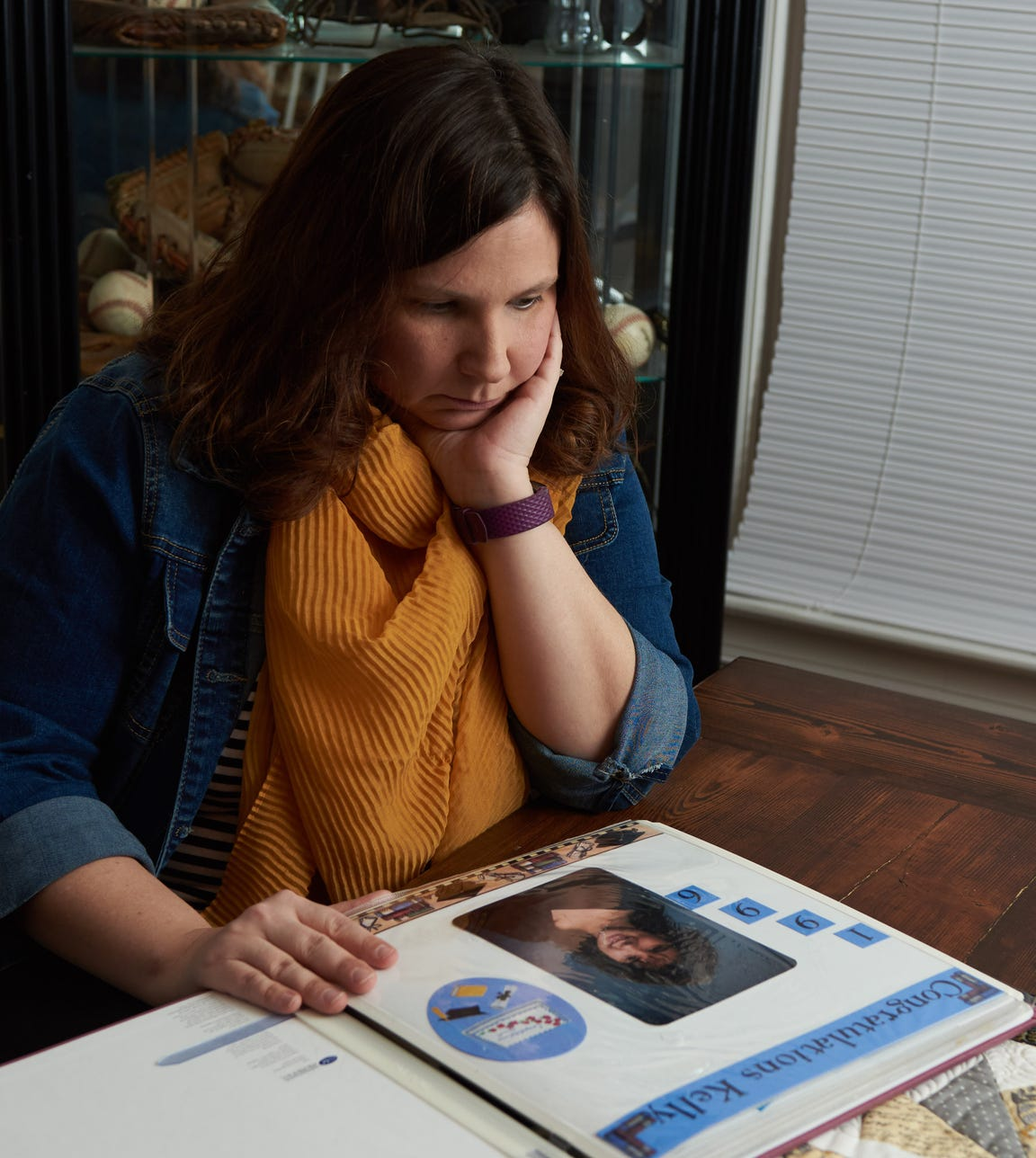 Kelly Haines looks at a photograph of herself as a child. Haines alleges she is a victim in the 1990s child exploitation case in Pennsylvania perpetrated by a teacher, John Longaker. Seen at her home in Quakertown, Pennsylvania, on Thursday, Jan. 10, 2019.