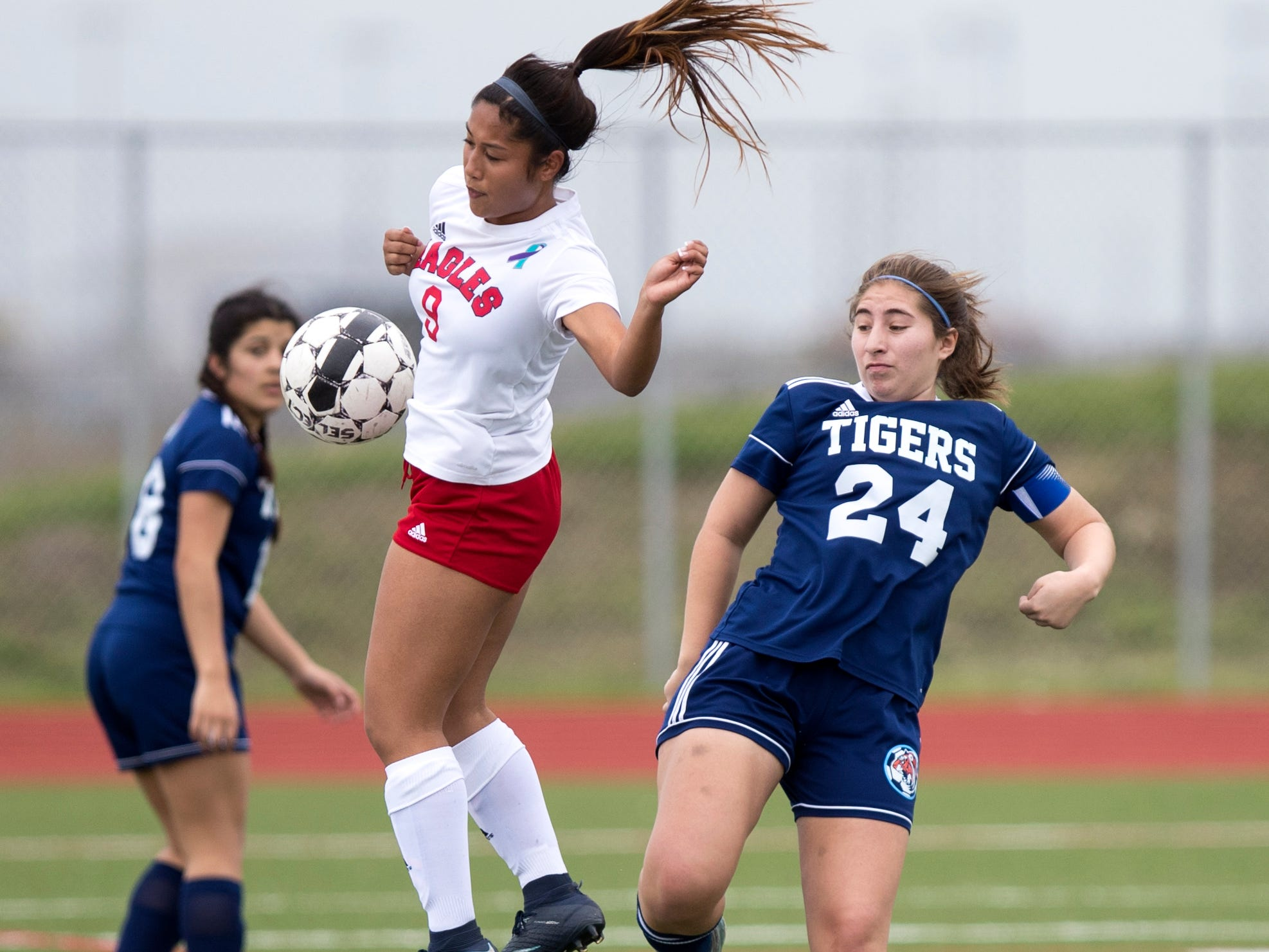 Veterans Memorial's Maricris Albarda (9) and Carroll's Nicole Escamilla (24) go after the ball in the Mira's Soccer Tournament at Veterans Memorial High School on Friday, January 11, 2019. The Eagles won the game 5-0.