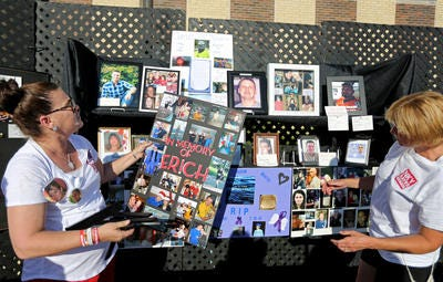 In 2016, Kimberly Wright (left) and Mae Corbin assemble a memorial of photos of people who'd died from heroin at a grassroots fundraiser in Independence, Kentucky.