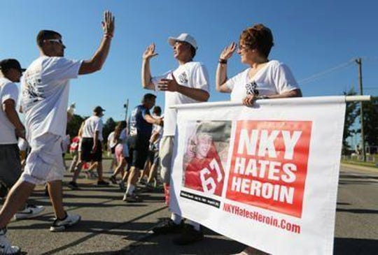 Eric and Holly Specht carry a banner for their nonprofit, NKY Hates Heroin, with a photo of their son who died from overdose in Fort Thomas, during a fundraiser 5K in Northern Kentucky in 2015.