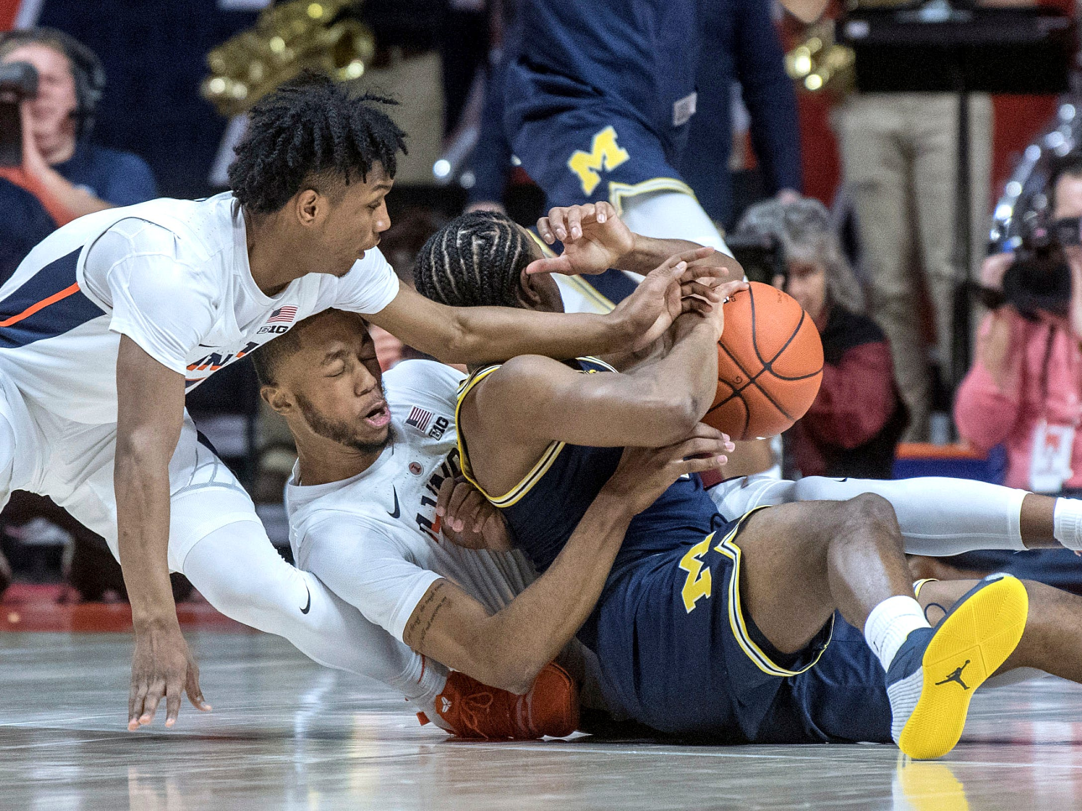 Illinois guards Trent Frazier and Alan Griffin battle for the ball with Michigan guard Zavier Simpson, right, during the first half of an NCAA college basketball game in Champaign, Ill., Wednesday, Jan. 10, 2019.