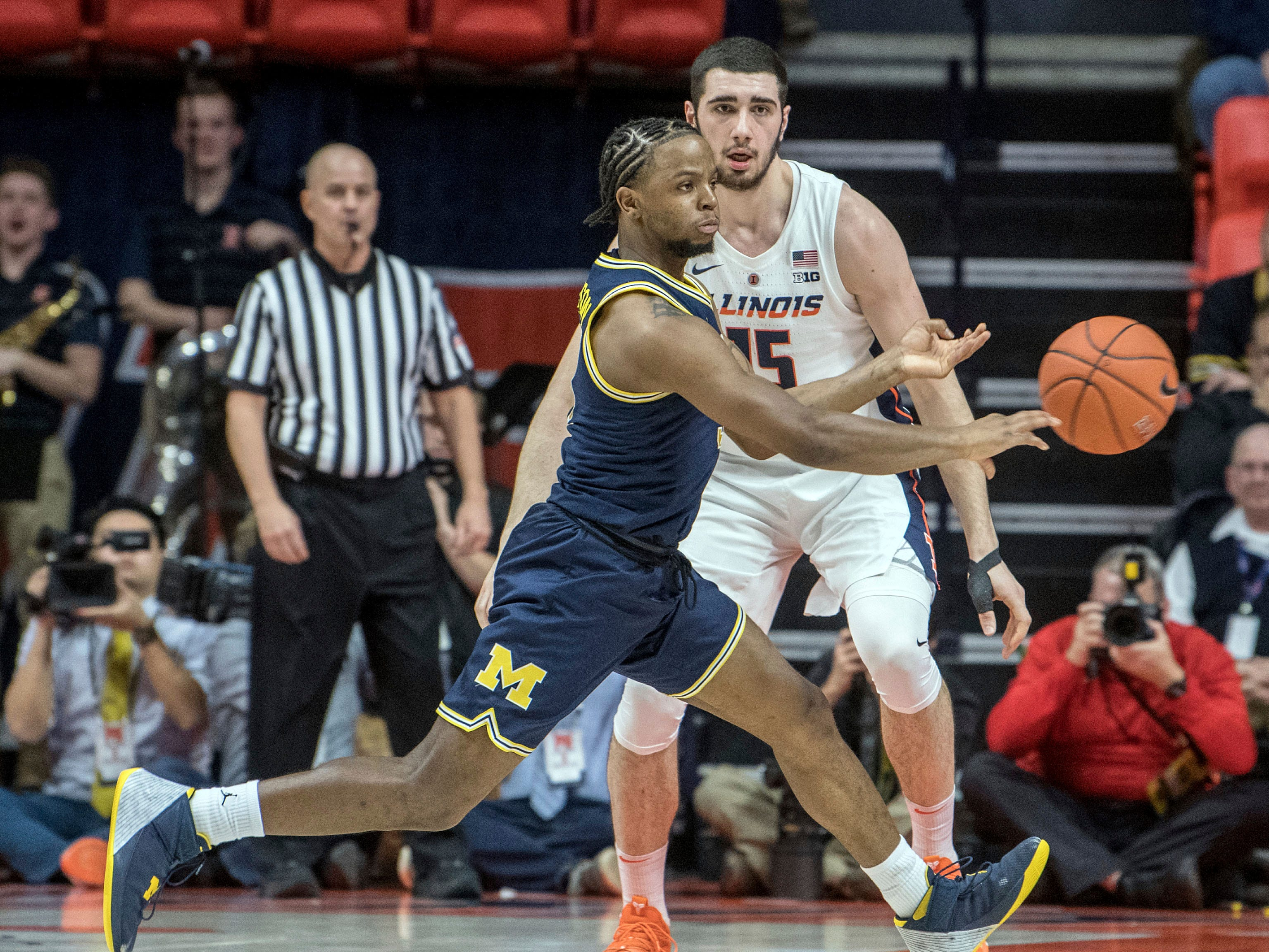 Michigan guard Zavier Simpson passes the ball as Illinois forward Giorgi Bezhanishvili (15) defends during the first half of an NCAA college basketball game in Champaign, Ill., Wednesday, Jan. 10, 2019.