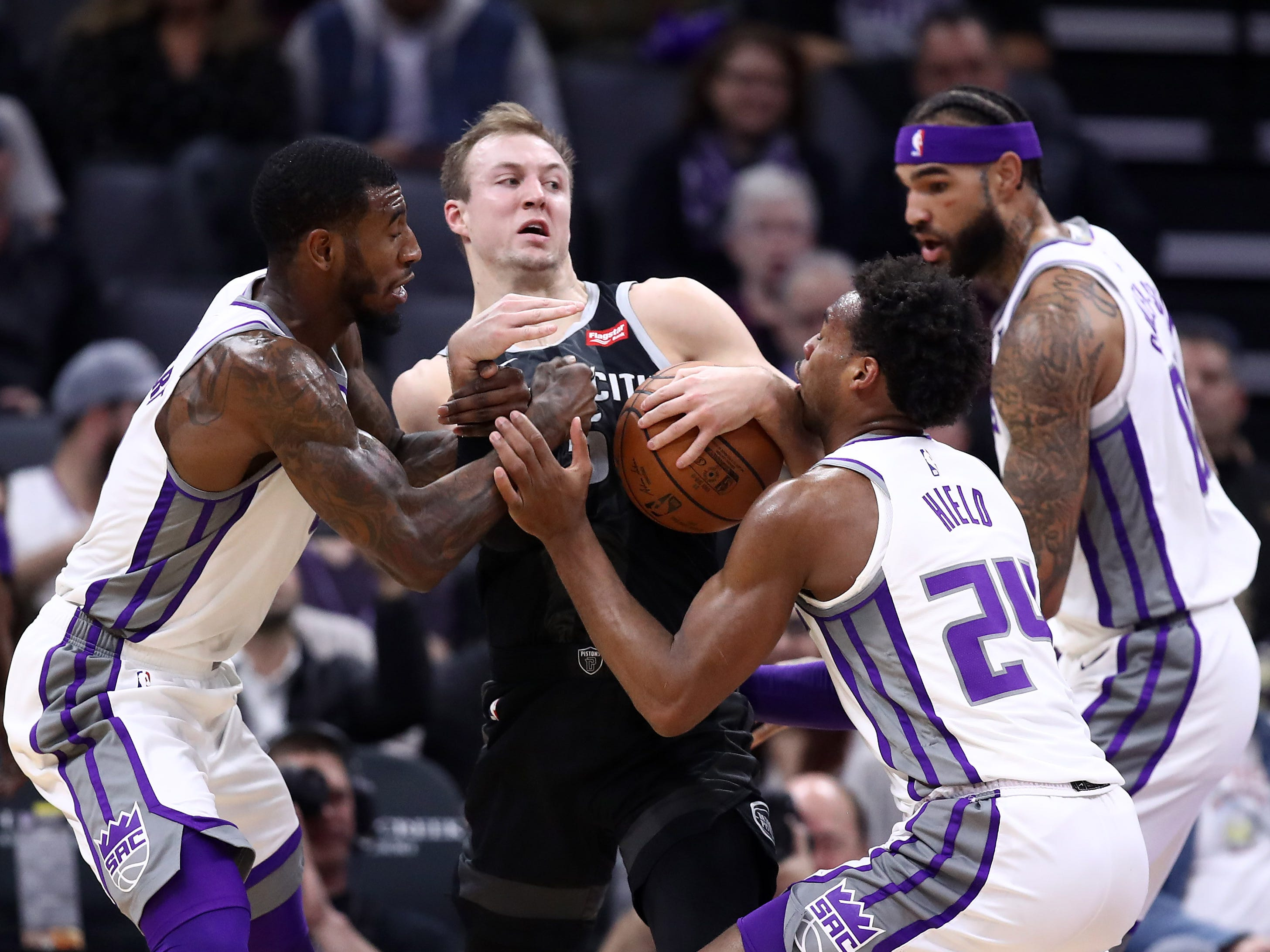 Luke Kennard #5 of the Detroit Pistons is surrounded by Iman Shumpert #9 and Buddy Hield #24 of the Sacramento Kings at Golden 1 Center on January 10, 2019 in Sacramento, California.