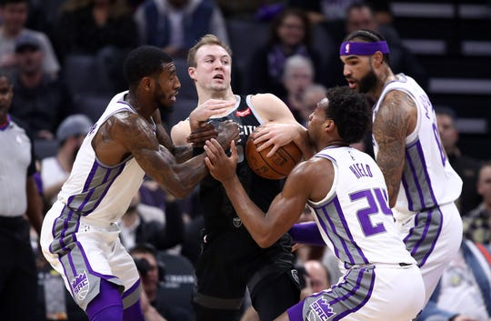 Pistons' Luke Kennard is surrounded by Iman Shumpert (9 ) and Buddy Hield (24) on Jan. 10 in Sacramento, Calif.