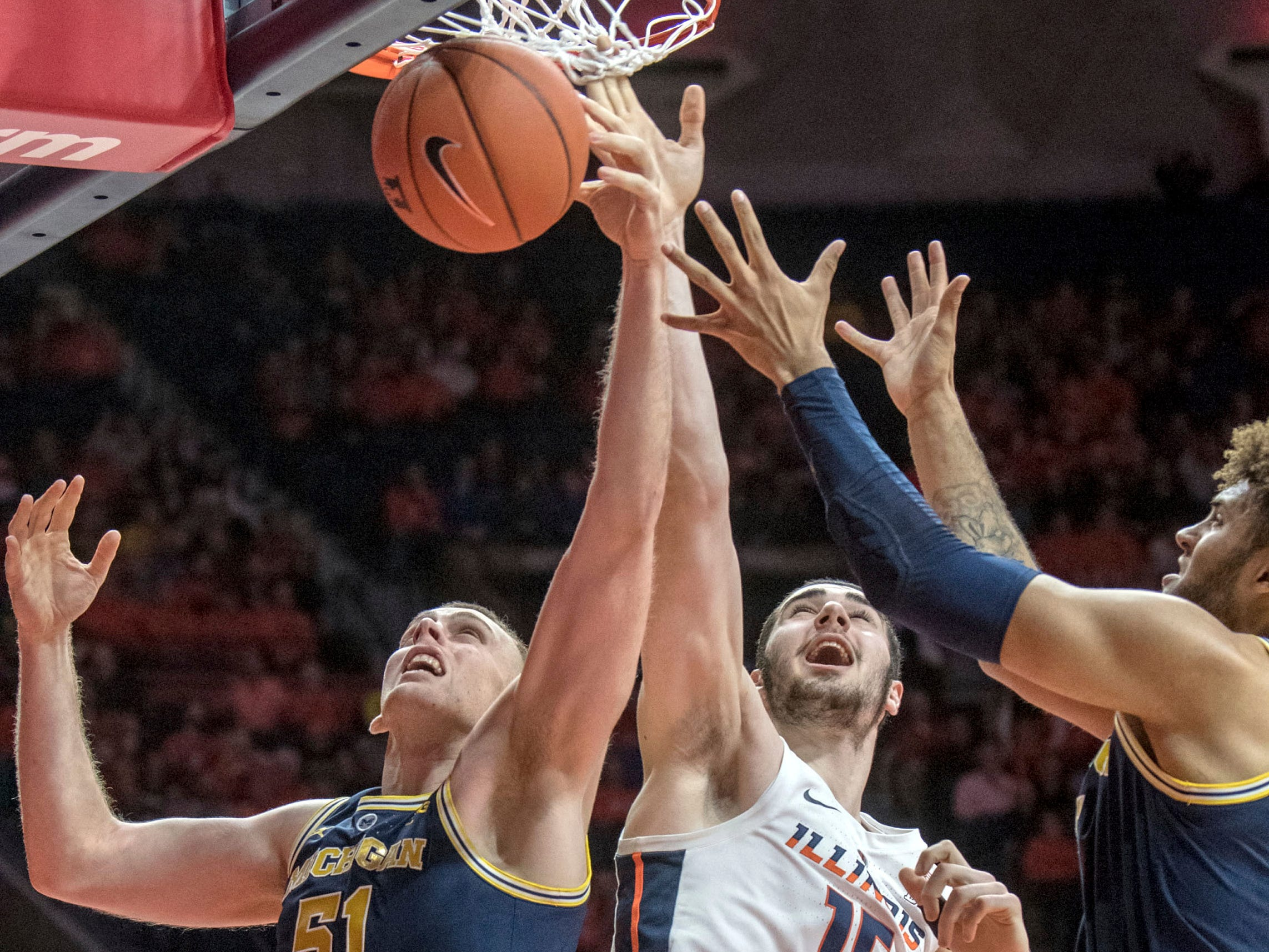 Michigan forward Austin Davis (51) and Michigan forward Isaiah Livers (4) go up for a rebound with Illinois forward Giorgi Bezhanishvili during the first half of an NCAA college basketball game in Champaign, Ill., Wednesday, Jan. 10, 2019.