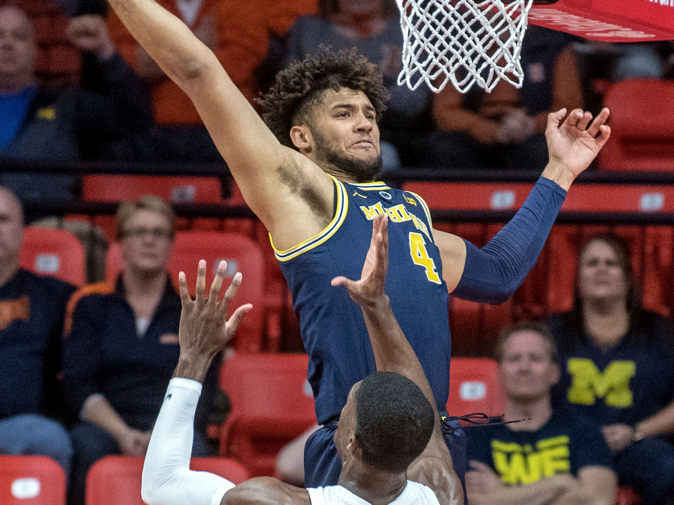 Michigan forward Isaiah Livers (4) goes up for a rebound over Illinois forward Kipper Nichols (2) during the first half of an NCAA college basketball game in Champaign, Ill., Wednesday, Jan. 10, 2019.