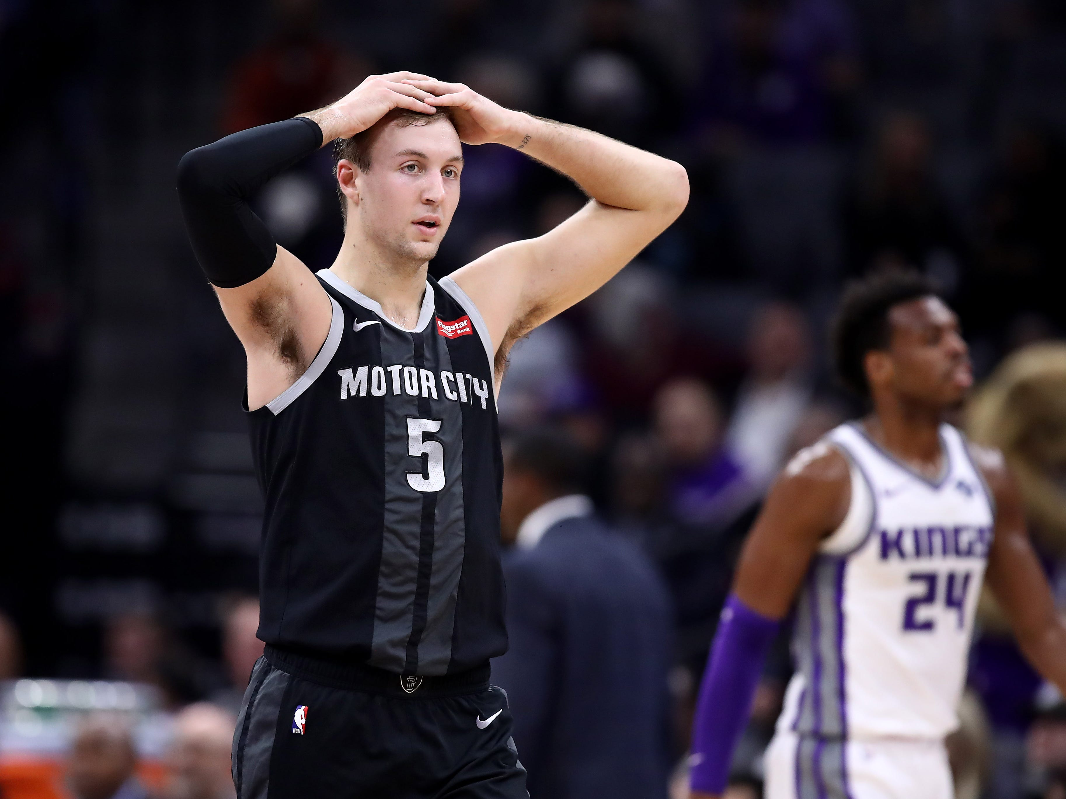 Luke Kennard #5 of the Detroit Pistons walks back down court with his hands on his head during their game against the Sacramento Kings at Golden 1 Center on January 10, 2019 in Sacramento, California.