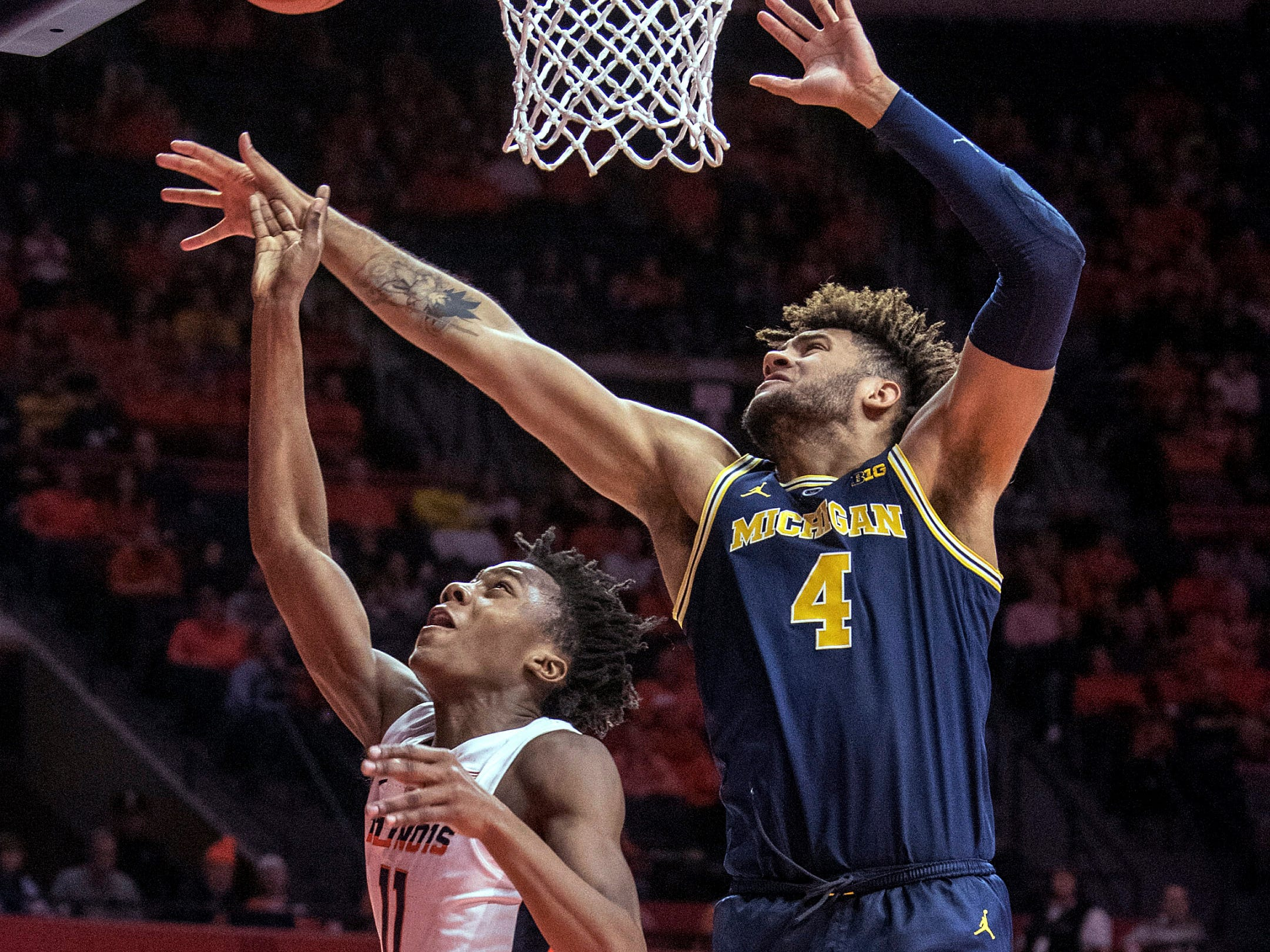 Illinois guard Ayo Dosunmu (11) shoots next to Michigan forward Isaiah Livers (4) during the first half of an NCAA college basketball game in Champaign, Ill., Wednesday, Jan. 10, 2019.