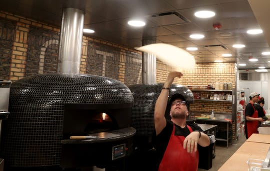 Bruno DiFabio, who developed the Mootz menu, tosses pizza dough inside the establishment.