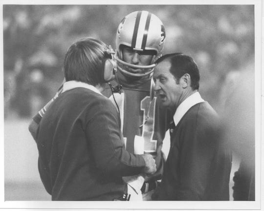 Detroit Lions coach Rick Forzano, right, talks with quarterback Greg Landry and an assistant during a game on Sept. 26, 1976.