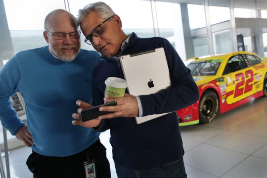 Kumar Galhotra, president of Ford North America, right, shows photographs to Steve Kraning at Ford World Headquarters in Dearborn of the race where Joey Logano won the Nascar title for Ford this year.