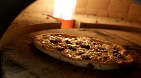 An inside-the-oven view of a Starry Hope pizza containing meatballs, caramelized onions, ricotta, mozzarella and pesto.