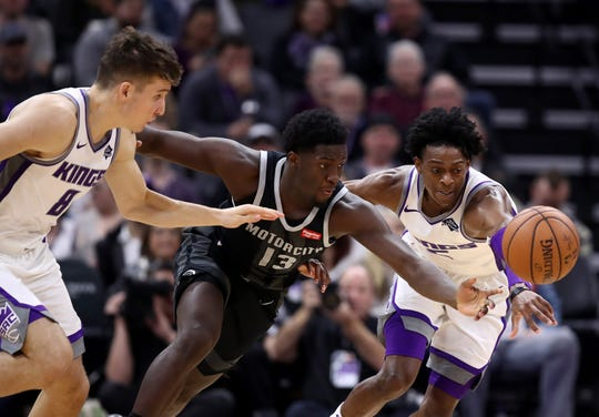 Bogdan Bogdanovic (8) and De'Aaron Fox of the Kings go for a loose ball against Khyri Thomas of the Pistons.