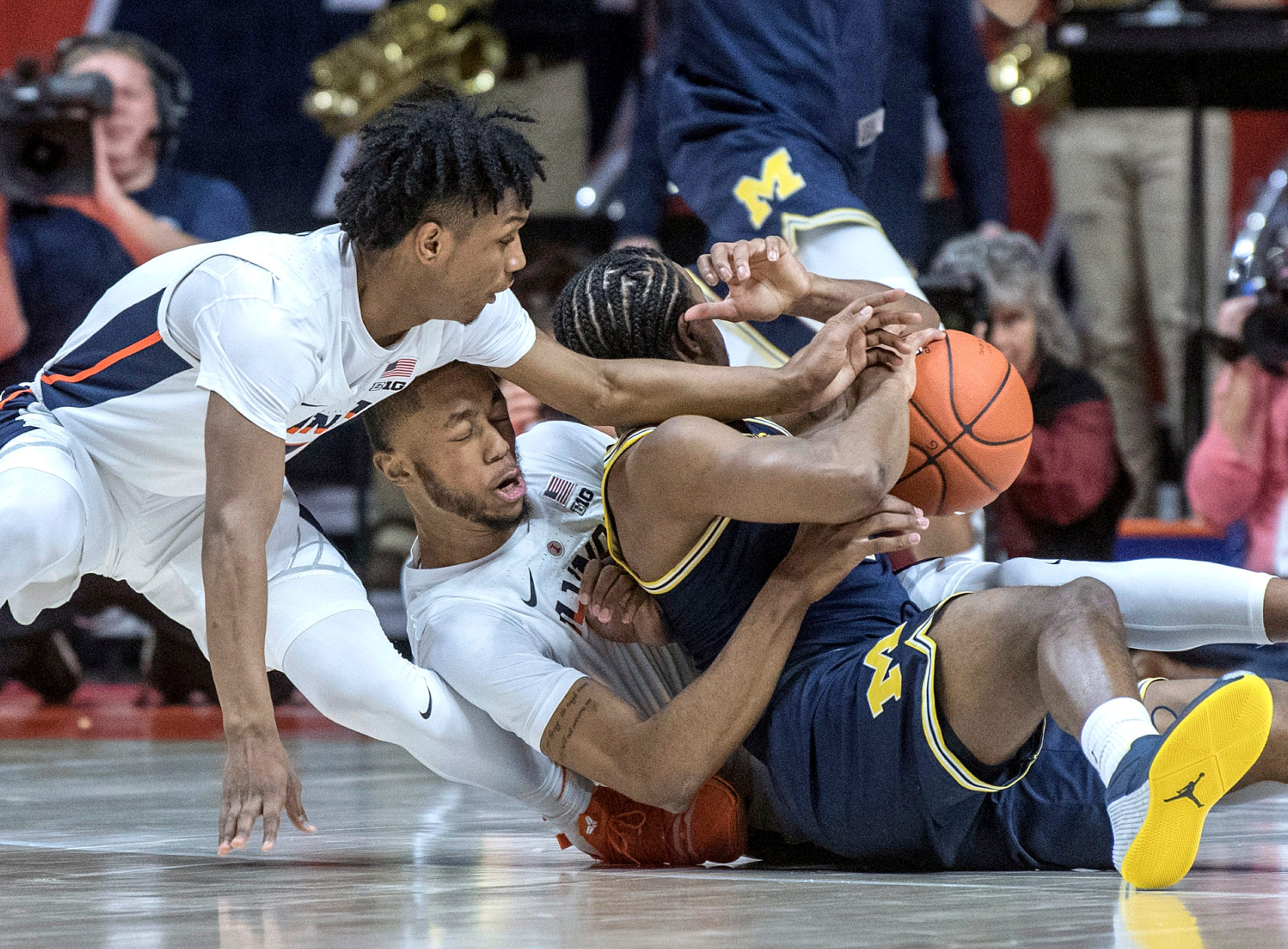 Illinois guards Trent Frazier and Alan Griffin battle for the ball with Michigan guard Zavier Simpson, right, during the first half.